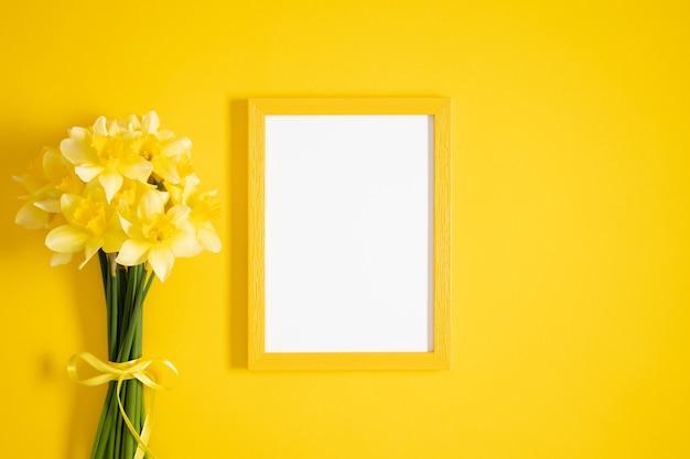 Желтые цветы нарциссов и фоторамка на желтой плоской планировке, вид сверху