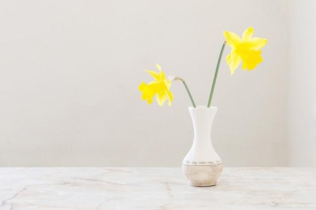 Желтые нарциссы в вазе на мраморном столе