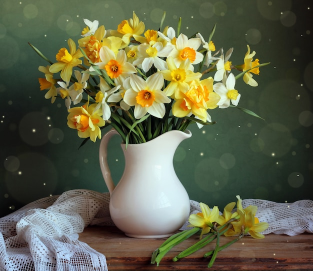 Yellow daffodils in a white pitcher on the table.