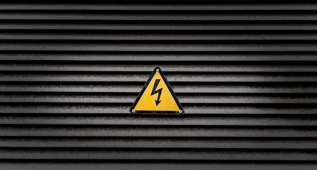 Yellow danger sign on a black striped wall