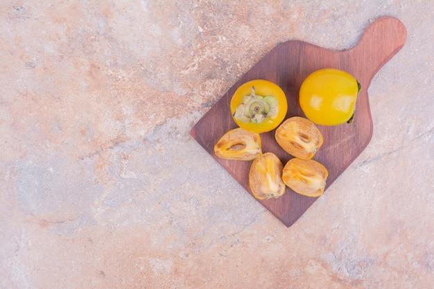 Prugne gialle della data sul vassoio di legno.