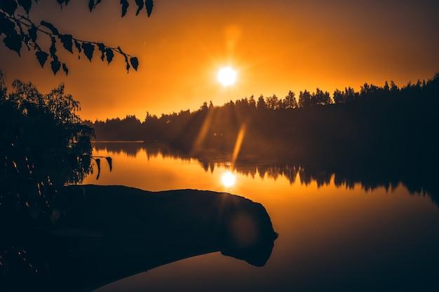 氾濫した採石場、ロマンス山脈の湖の上の黄色い夜明け