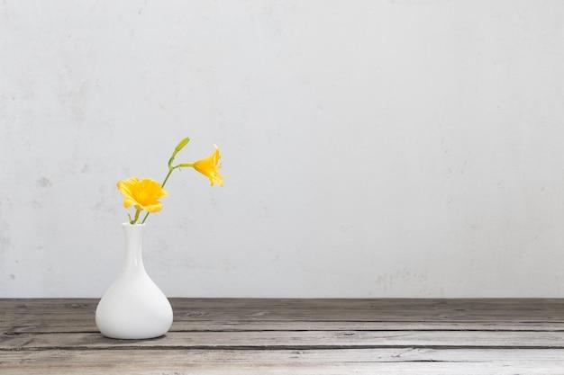 나무 테이블에 흰색 꽃병에 노란색 하루 백합 꽃