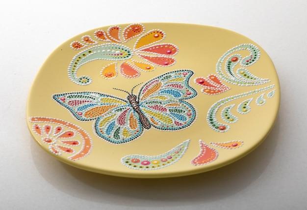 Желтая декоративная тарелка для внутренней отделки на белом фоне