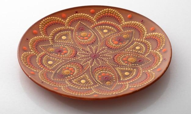 Yellow decorative plate with a mandala pattern on a white background