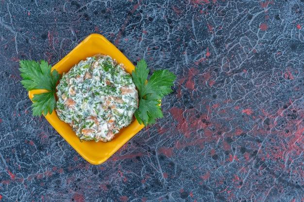 Un piatto fondo giallo con deliziose insalate ed erbe aromatiche.