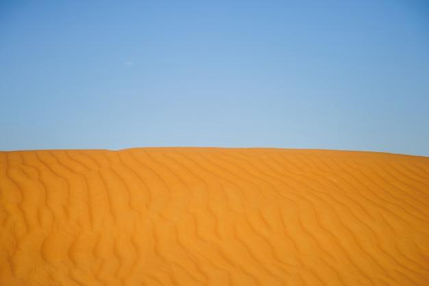 黄色の砂漠の砂丘と空。