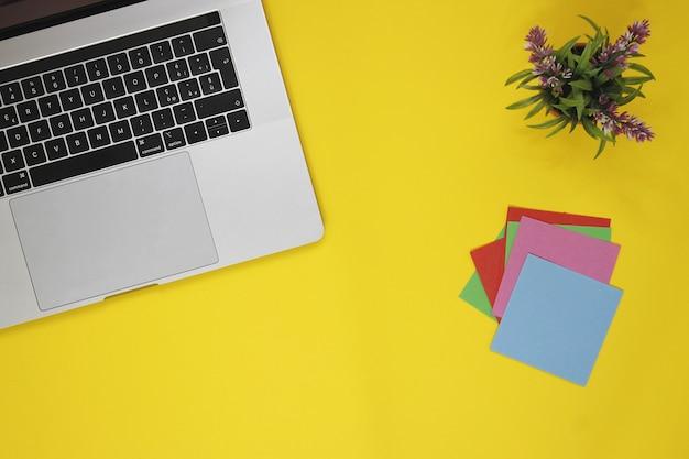 Желтый стол и серый ноутбук. желтый фон с видом сверху и стикерами для заметок