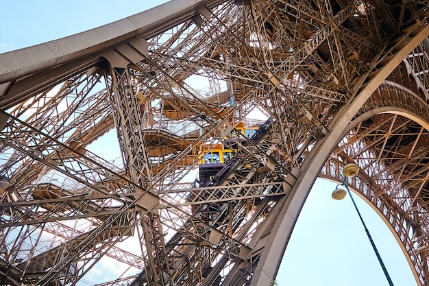 Yellow diagonal elevator inside a metal support of eiffel tower in paris in france