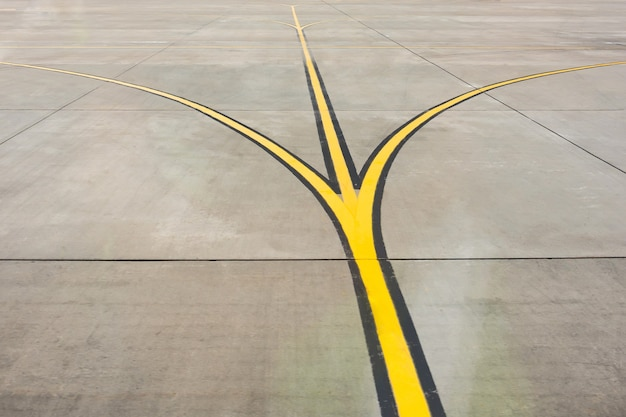 Yellow direction strips fork close up on an airfield runway.