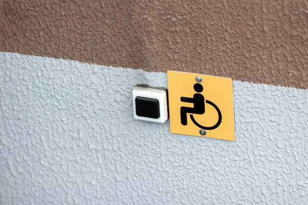 Yellow disabled sign attached to the wall.