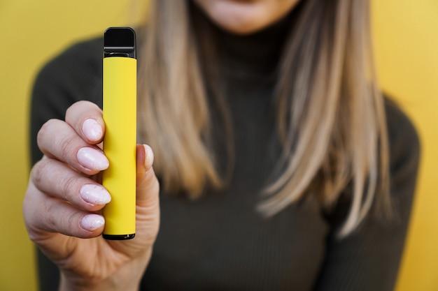 Желтая одноразовая электронная сигарета в женской руке. ярко-желтый фон. вейп со вкусом дыни, ананаса или лимона