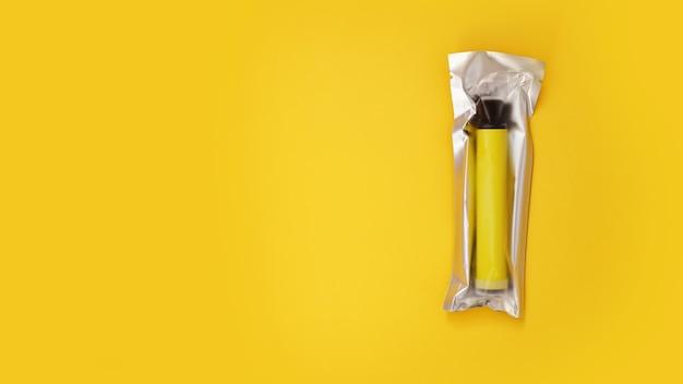 黄色の壁に梱包された黄色の使い捨て電子タバコ