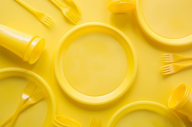 Yellow disposable picnic utensils. save planet.