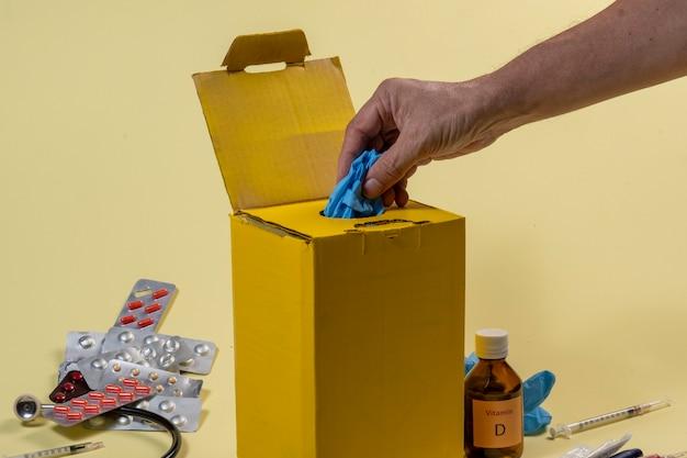 病院または家庭内の汚染または感染性製品用の黄色の廃棄ボックス。保護手袋をはめた手