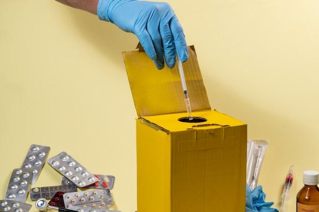 病院または家庭内の汚染または感染性製品用の黄色の廃棄ボックス。注射器を置く手