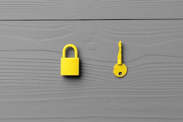 Yellow door key on gray wooden background