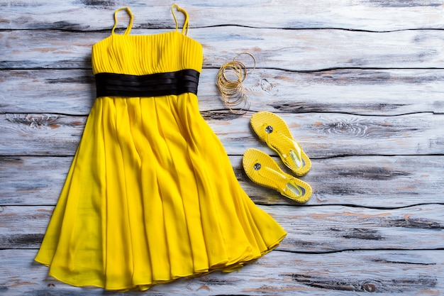 Yellow dress and flip flops. casual dress, footwear and bracelets. lady's bright summer apparel. get ready for upcoming season.
