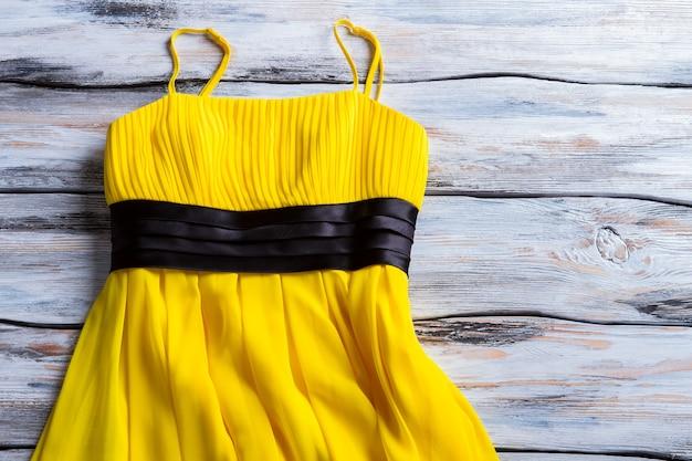 Желтое платье на тонких бретелях. яркое платье на деревянных фоне. женская одежда на белом столе. цвет лета.