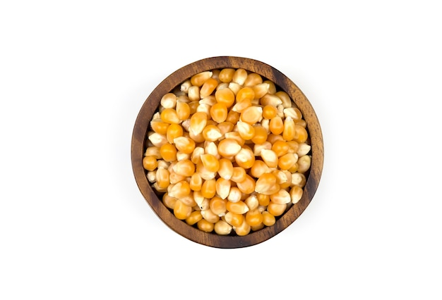 白い背景の上の木製のカップに黄色の乾燥トウモロコシの果実