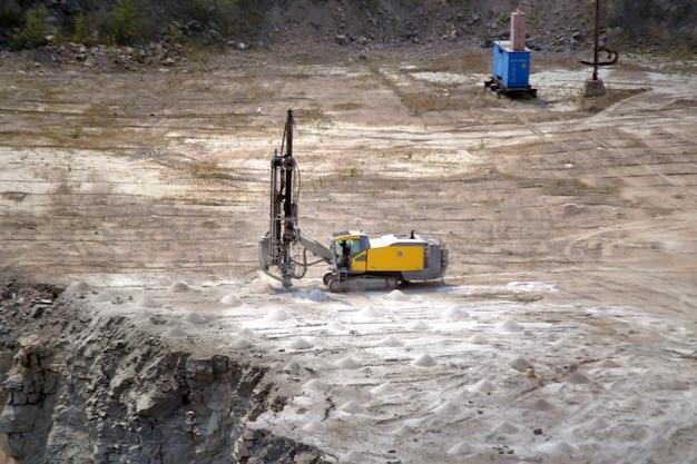 Yellow drill machine closeup on a granite quarry