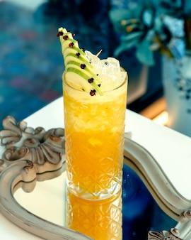 ミラー上の氷とリンゴのスライスと黄色の飲み物
