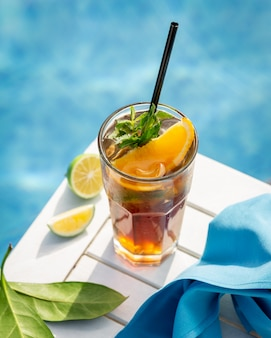 Yellow drink with orange,lemon and mint leaves by the pool.