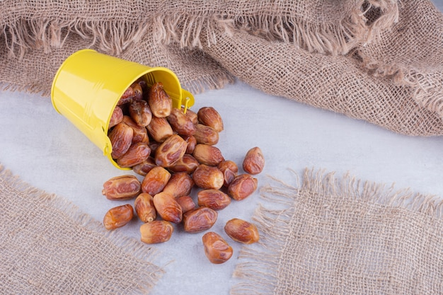 Yellow dry dates in a cup on concrete surface