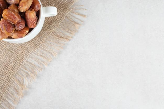 セラミック皿の黄色い乾燥ナツメヤシ。