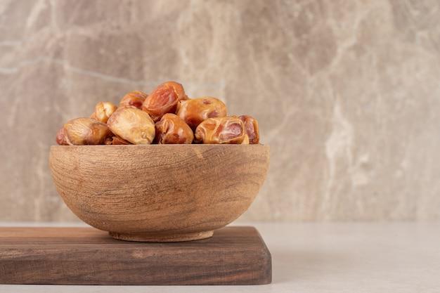 木製の大皿に分離された黄色の乾燥ナツメヤシ。