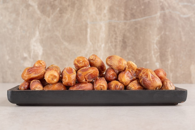 Yellow dry dates isolated on a wooden platter.