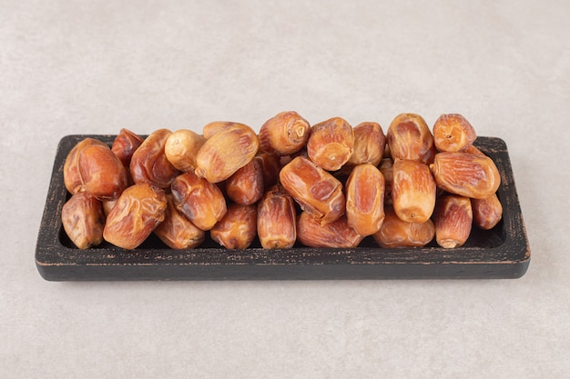 Yellow dry dates on a wooden platter.