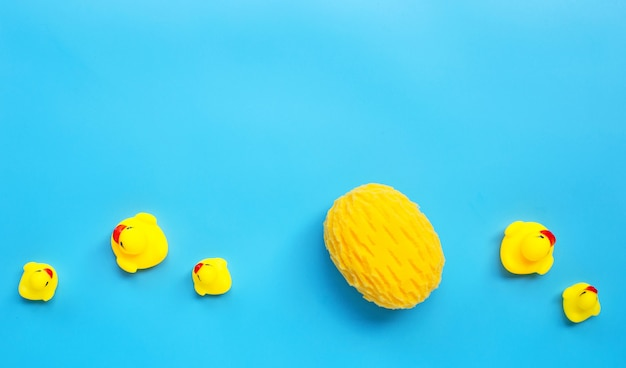 Yellow duck toys with yellow sponge on blue background. kids bath concept.
