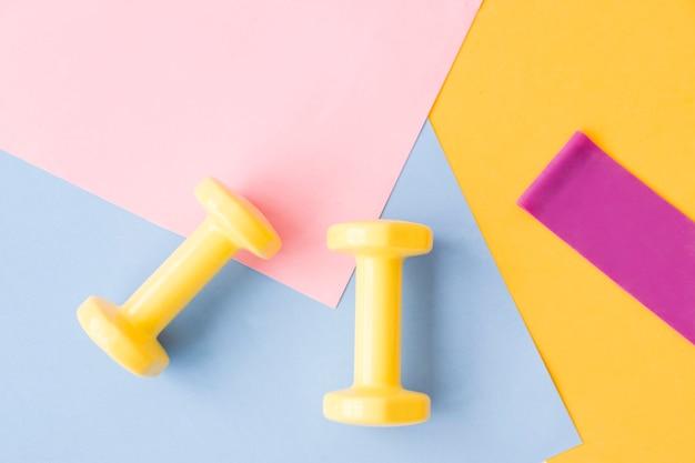 Желтый цвет гантели на розовом, синем и желтом коврике. дизайн спортивного плаката или баннера в модных цветах 2021 года