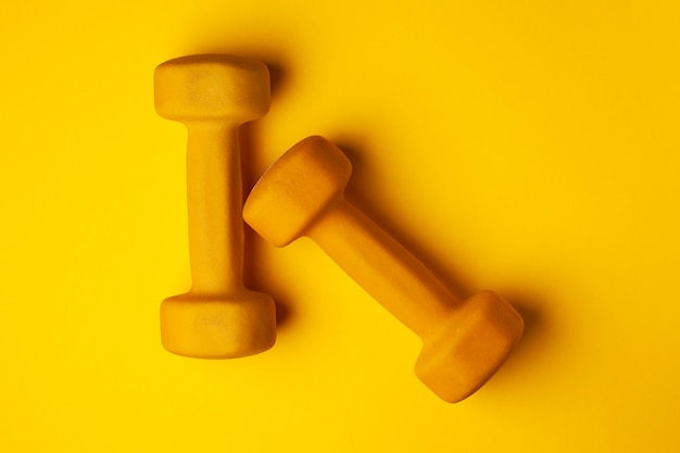 Yellow dumbbells lie on a yellow background, the concept of summer, training, sports