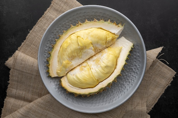 暗いテクスチャ背景、果物の王の金属板の黄色のドリアンmonthong肉