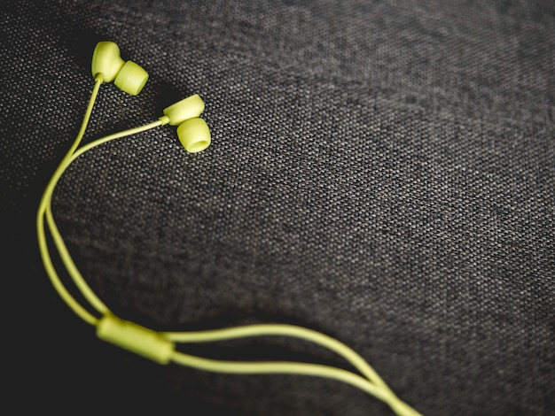 Yellow earbuds on the dark brown sofa background.