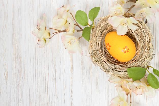 짚 둥지와 흰색 나무 바탕에 꽃 지점에 노란색 부활절 달걀. 상위 뷰, 텍스트를위한 공간이있는 평면 배치.