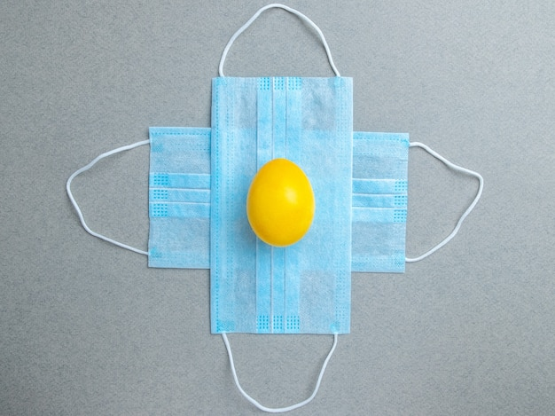 黄色のイースターエッグは灰色の背景の青い医療マスクの上にあります