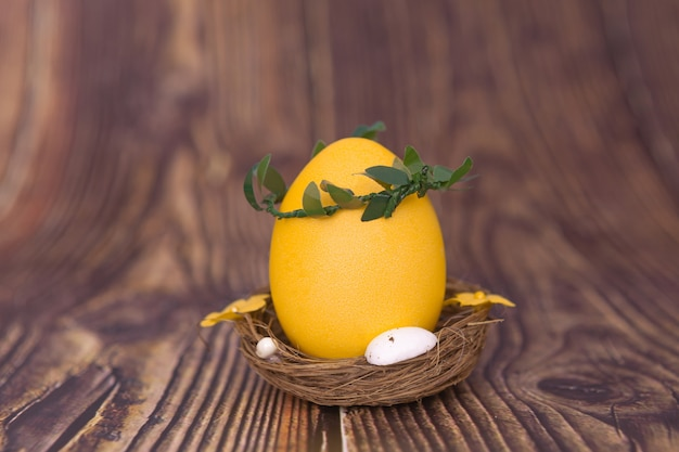 Yellow easter egg in a nest on wooden background
