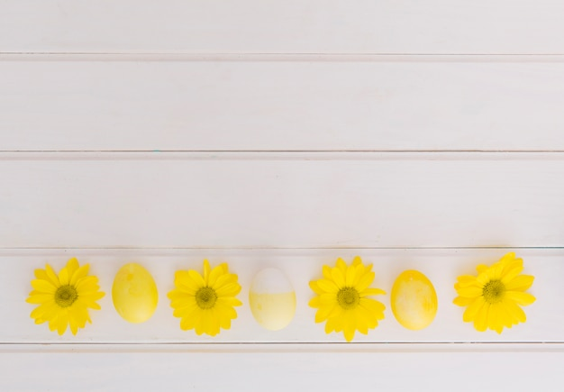 Yellow easter eggs and flowers on desk