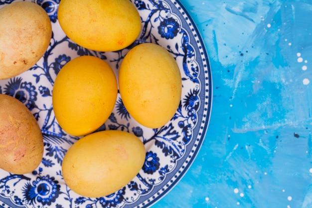블루 테이블에 접시에 노란색 부활절 달걀