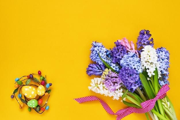 Желтый пасхальный стол. весенние цветы и декоративные пасхальные яйца. копирование пространства, вид сверху.