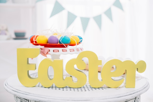 Yellow easter text in front of colorful easter eggs on cakestand