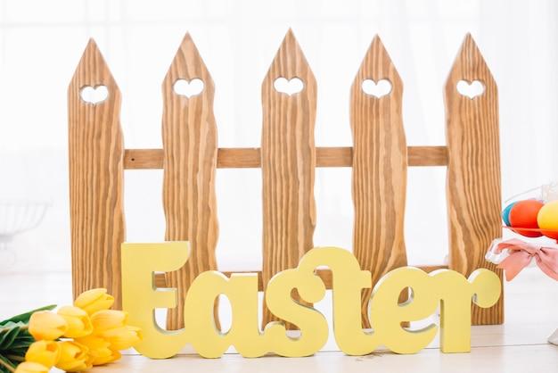 Желтое пасхальное слово перед деревянным забором в форме сердца с цветами тюльпана