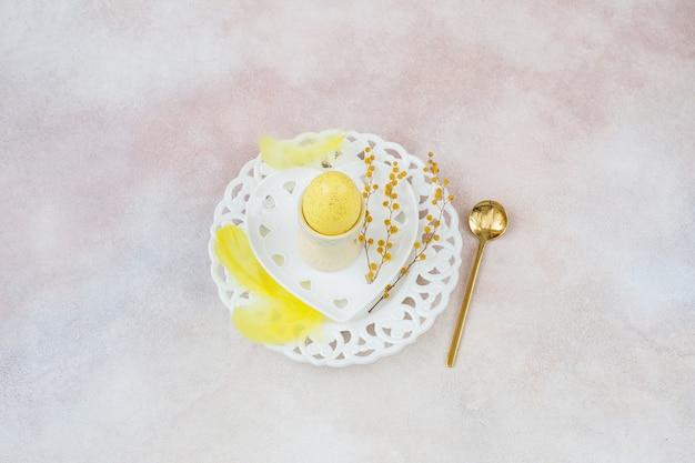 プレート、スプーン、イースターの装飾の黄色い卵
