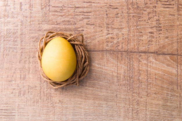 Yellow egg on a nest of paper thread, wooden texture, easter concept