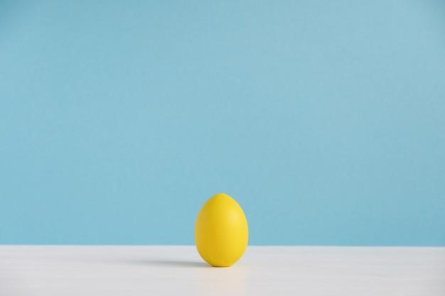 水色の壁に黄色い卵。イースター、おめでとう。最小限のイースター。