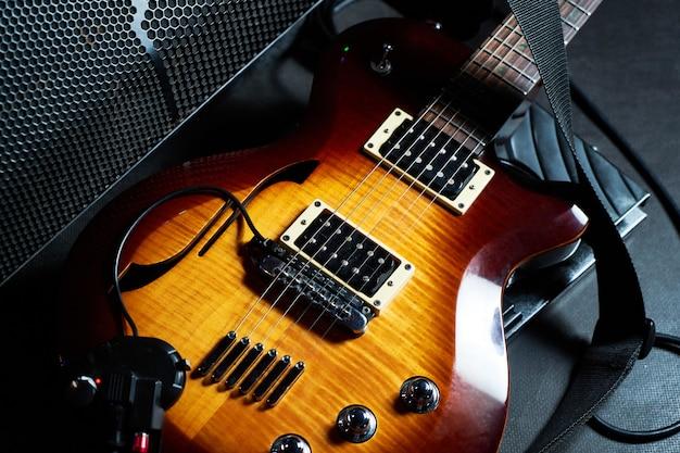 黄色のエレクトリックギターと暗い背景に黒のアンプクローズアップ