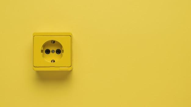 노란색 배경에 노란색 전기 콘센트입니다. 텍스트를 위한 공간입니다.